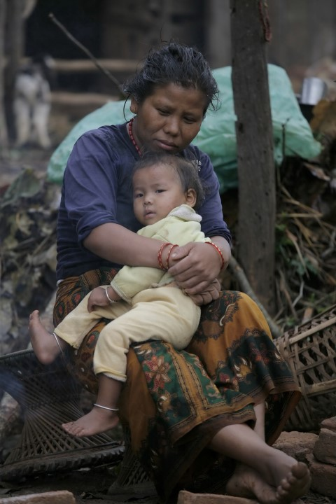 """This hand out photo taken and released by Caritas Internationalis on May 2, 2015 shows a woman and a child after their house has been destroyed by the earthquake in Gorkha. AFP PHOTO / MATTHIEU ALEXANDRE / CARITAS INTERNATIONALIS -- EDITORS NOTE -- RESTRICTED TO EDITORIAL USE - MANDATORY CREDIT """" AFP PHOTO/ MATTHIEU ALEXANDRE/CARITAS INTERNATIONALIS"""" - NO MARKETING NO ADVERTISING CAMPAIGNS -"""