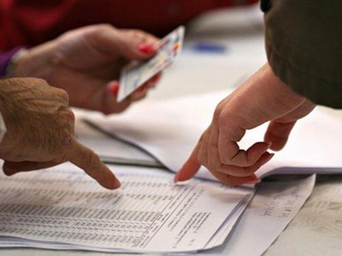 Doi membri ai comisiei de votare si un alegator se uita pe listele cu alegatori la scoala 194 din Bucuresti, duminica, 30 noiembrie 2008. Un numar de aproximativ 18 milioane de cetateni cu drept de vot sunt asteptati, duminica, la urne, pentru a trimite in Parlament 315 deputati si 137 senatori, premiera scrutinului constituind-o sistemul uninominal. DIANA IURKIEWICZ / MEDIAFAX FOTO