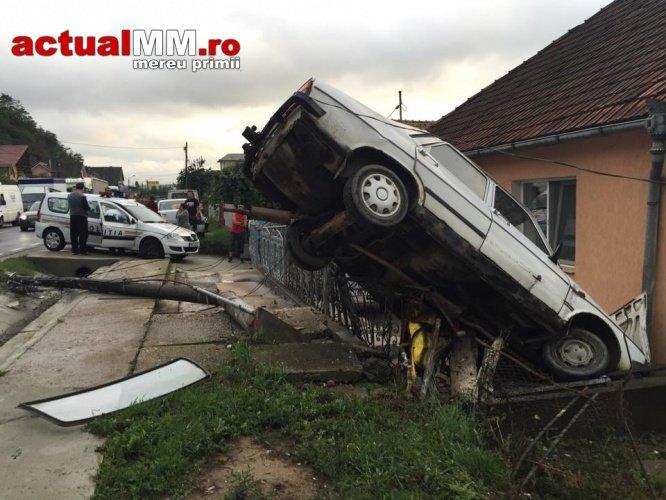 A rupt un stâlp și s-a urcat cu Dacia pe o casă (Foto)