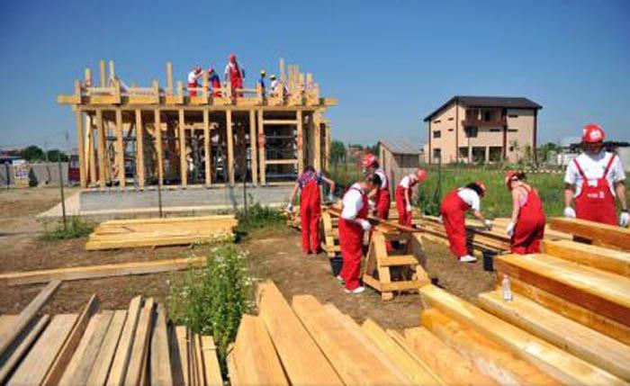 Sute de voluntari vor construi 40 de case în 5 zile