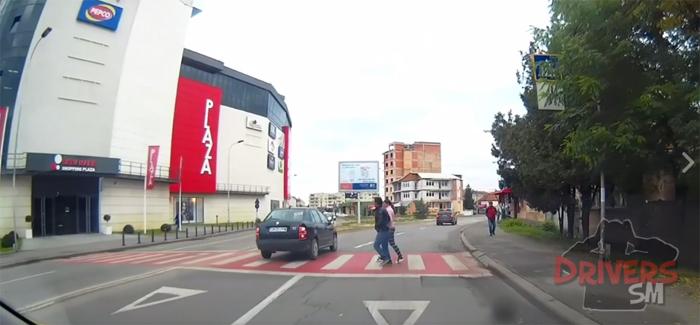 Doi pietoni neatenți, la un pas să fie luați pe capota unei mașini (Video)