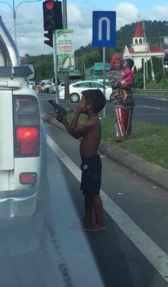 Copil cu un pistol in mana, pe post de cersetor. Se intampla ziua in amiaza mare (Foto)